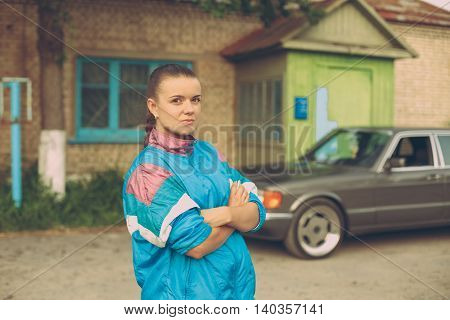 The girl in the nineties. On the background of old car