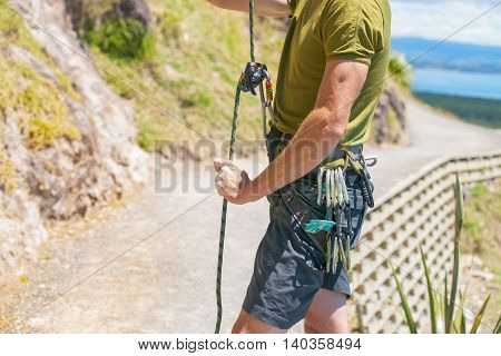 Man readies for climb up a rock face with harness and rope and carabiners organised for the ascent