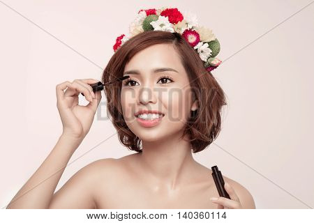 Sensual portrait of a spring woman with flowers on her head using mascara