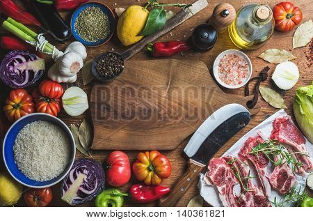 Ingredients for cooking dinner. Raw uncooked lamb meat chops, rice, oil, spices and vegetables over wooden background, top view, copy space