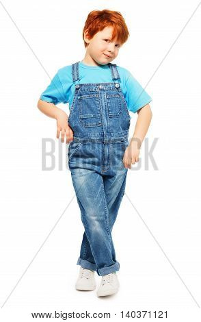 Full-length photo of cute redheaded five years old boy in overall and blue t-shirt, isolated on white