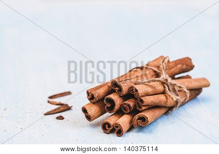 Ground cinnamon, cinnamon sticks, tied with jute rope on old wooden background in rustic style selective focus