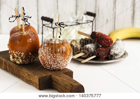 Taffy apples, milk and glazed banana pops over white table. Kid sweet treats for Halloween party. Selective focus
