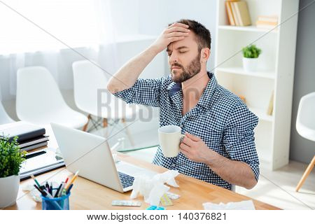 Sick Businessman With Temperature And Headache Working In Office