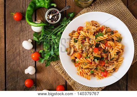 Vegetarian Vegetable Pasta Fusilli With Zucchini, Mushrooms And Capers In White Bowl On Wooden Table
