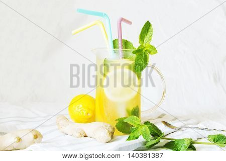 Lemonade with ginger and mint in kitchen. Summer drinks. Home made ginger lemonade on striped napkin or towel. Healthy drink lemonade.