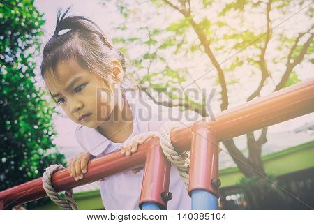 Asian kindergarten student climbing up the top of the playground looking lonely