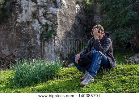 UPPER GALILEE - JANUARY 16: Teenager sits on the grass near the rock propping up head on his hand in Upper Galilee, Israel on January 16, 2016