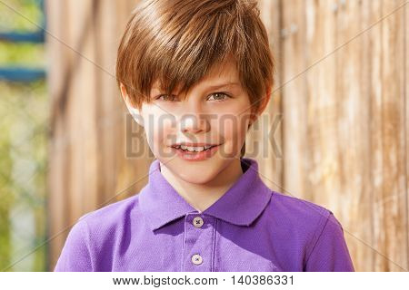 Close-up portrait of ten years old brunette boy in purple polo shirt, outside in summertime