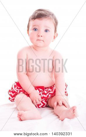Beautiful baby girl in red pants on white background.