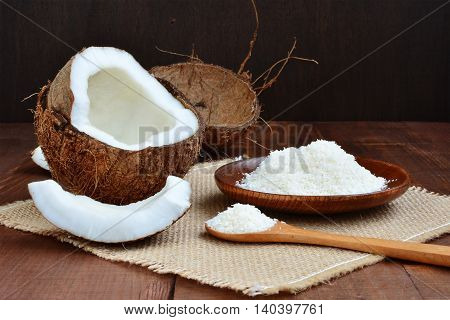 Cracked coconut and grated coconut flakes on dark background.