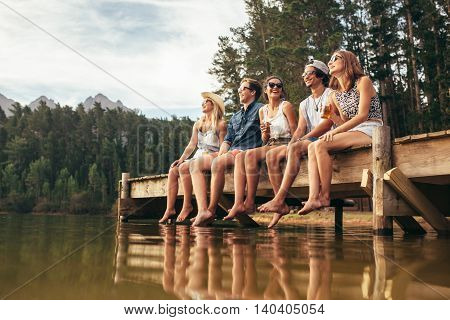 Group Of Friends Sitting On Jetty At Lake
