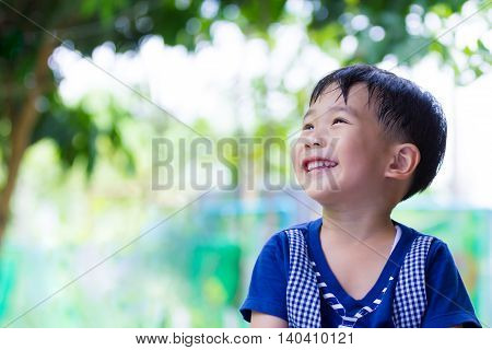Happy Asian Boy Looking Up At Park. Outdoors In The Day Time, Travel On Vacation.