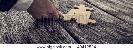 Wide crop on single hand coming from formal business suit attaching puzzle piece on old wooden table vintage effect toned image.