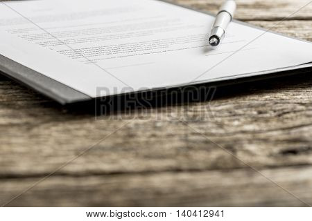 Uncapped pen on top of typewritten piece of paper on clipboard. Includes out of focus foreground with copy space.