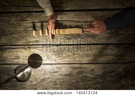 Businessman preventing the domino effect chain reaction by inserting his hand into a line of falling dominoes overhead view on a rustic table lit by a single lamp with copy space.