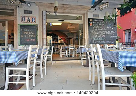 SIRMIONE ITALY - JULY 14: Tables and chairs in the typical italian bar-restaurant in Sirmione Italy on July 14 2014. Sirmione is a resort on Garda lake in northern Italy.