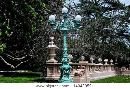 Newport Rhode Island - July 17 2015: Elaborate beaux art lamp post with round glass globes and fence with urns at The Breakers summer home of Cornelius Vanderbilt