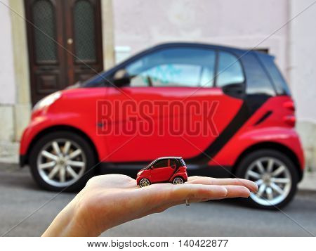 LISBON PORTUGAL - DECEMBER 9: Red Smart Car and the mini model in the same colour in the street of Lisbon on July 5 2008. Smart is a city car with company headquarters in Germany.