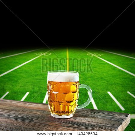 Glass of beer on football field stadium background