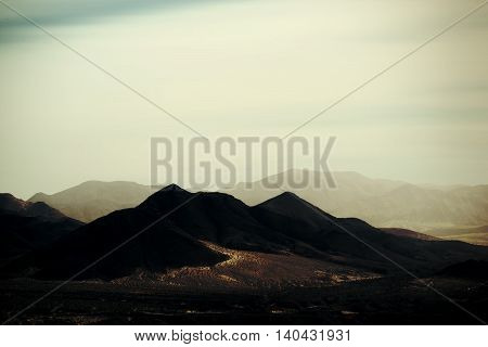 Top peaks and ranges of rough darker and brighter mountains in the Mojave Desert near Death Valley Junction.