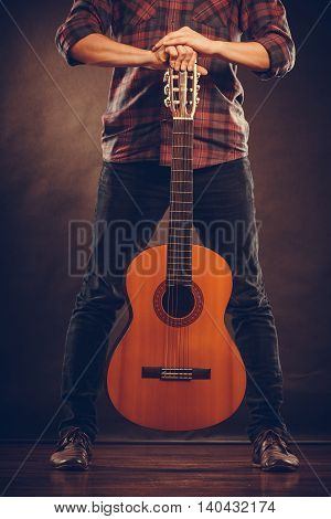 Music hobby concept. Guitarist is standing with wooden guitar. Man is holding the instrument. poster