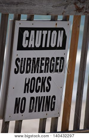 Caution Sign on Beach Boardwalk Submerged Rocks, No Diving