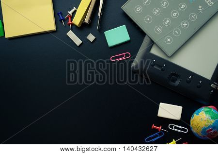 Back to school concept. School supplies with calculator and ebook on blackboard background. Back to school concept with stationery. Schoolchild and student studies accessories. Top view.