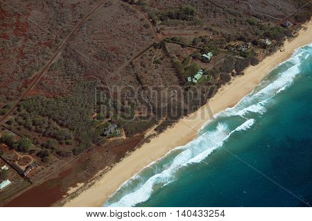 Aerial of Northwest coast of Molokai with waves crashing into long sandy beach and surrounding area of island with roads largely undeveloped. April 2016.