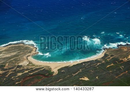 Aerial of coastline of Molokai with waves crashing into Mo'omomi beach rocky shore and surrounding area of island with dirt roads largely undeveloped. April 2016.