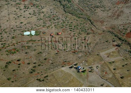 Aerial of countryside with a few homes on Molokai with dirt roads largely undeveloped with trees and bushes. April 2016.