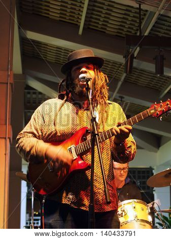 HONOLULU HI - JANUARY 29: Lead singer of Guidance Band plays guitar and sings as he Jams with band on stage at Mai Tai Bar in Ala Moana Shopping Center on January 29 2016 Honolulu Hawaii.