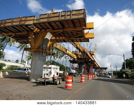 HONOLULU - NOVEMBER 29: HART Light Rail concrete guideway under construction in road center with 'Fuck Da Rail' written on side of machine in Pearlrigde on Oahu Hawaii on November 29 2015. HART is building a 8 billlion dollar railway linking Oahu communit