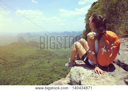 young woman backpacker sit on mountain peak cliff