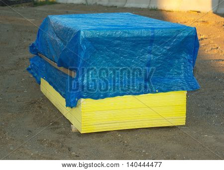 wooden stacked plywood or gyproc panels covered with a tarp on construction site