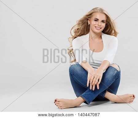 Beautiful Woman Blonde Curly Hair Jeans Fashion Full Length Sitting On Floor.
