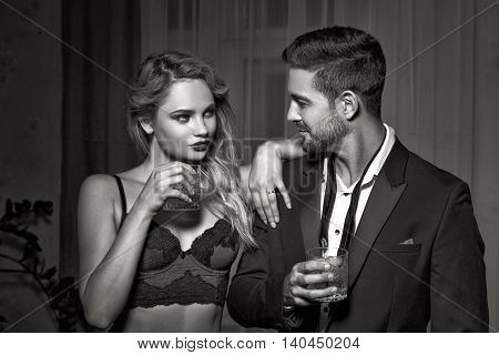 Sexy macho man with blonde woman in underwear and whiskey drinking together