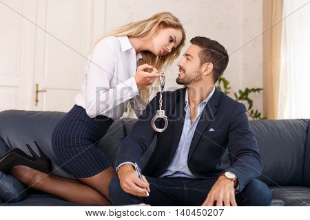 Businesswoman holding handcuffs for businessman in office