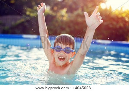 Happy little boy in goggles enjoying play in pool hurray summer holiday
