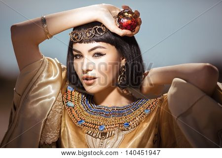 Photo of gorgeous woman with Cleopatra makeup, closeup portrait of beautiful female with stylish haircut agaist, young lady wearing fashionable golden necklace and holding magik ball outdoor, beauty salon consept