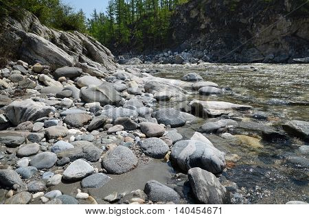 Rocky shore of Irkut River in its beginning in the Sayan Mountains in sunny day
