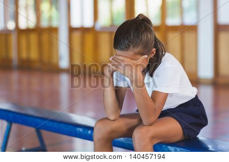Sad schoolgirl sitting alone in basketball court at school gym poster