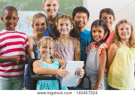 Portrait of teacher and kids in classroom at school