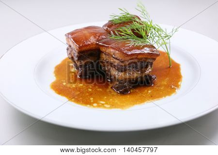 Braised pork meat in Chinese style with herbs on white plate