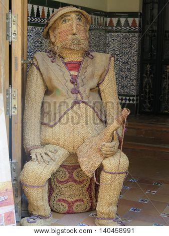 Woven male figure in dorway to handycraft shop in Ubeda Spain poster