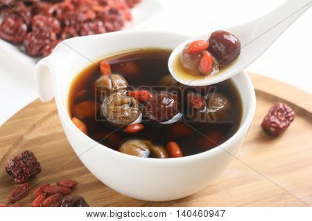 Wolfberry jujube tea longan in tea cup on wooden tray