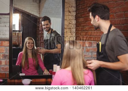 Handsome hair stylist with client at the hair salon