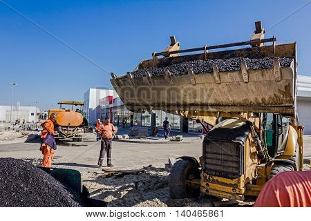 Zrenjanin Vojvodina Serbia - September 14 2015: Excavator in his lifted bucked is transporting asphalt at construction site.