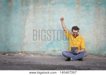 Jubilant man holding a tablet