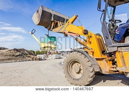 Excavator is moving over building site with raised up front bucket vibration plate compactor machine is hanging.
